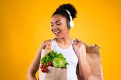 Svart flicka med livsmedel i isolerad hörlurar royaltyfria bilder