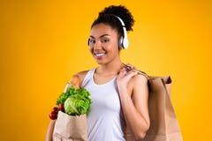 Svart flicka med livsmedel i isolerad hörlurar arkivfoto