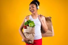Svart flicka med livsmedel i isolerad hörlurar royaltyfri fotografi