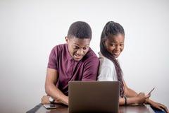 Svart flicka som framme sitter av bärbar dator s som ser på skärmen royaltyfri bild