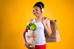 Svart flicka som rymmer livsmedelpåsar isolerade royaltyfri bild