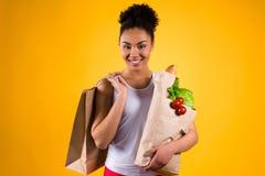 Svart flicka som rymmer livsmedelpåsar isolerade arkivbilder