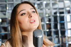 svart främre isolerad mikrofonsångare för bakgrund Härlig kvinna som sjunger på etappen bredvid mikrofonen arkivbild