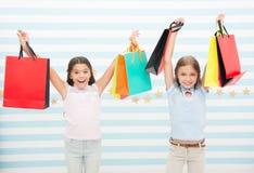 Svart fredag komma Ungeflickabarn med packar, når att ha shoppat dag Lyckliga flickavänner bär pappers- påsar bäst royaltyfria foton