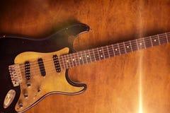 Svart gitarr på lädersignalljus en Royaltyfri Bild