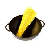 Svart gjutjärnkruka med rå pasta som isoleras Arkivbild