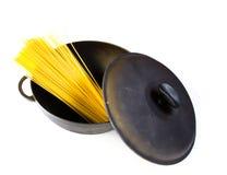 Svart gjutjärnkruka med rå pasta som isoleras Royaltyfria Foton
