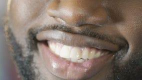 Svart grabb som ler till kameran med charmigt leende, vita tänder, toppen närbild stock video