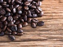 Svart grillade kaffebönor på åldrigt trä Royaltyfri Foto