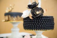 Svart guld- bröllopstårta Arkivbild