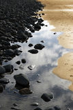 svart guld vaggar sanden Arkivbild