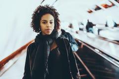 Svart gulligt flickaanseende på rulltrappan arkivbilder