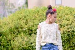 Svart-hövdad flicka som bär en blom- krona som framme står av naturbakgrund om den soliga dagen royaltyfri fotografi