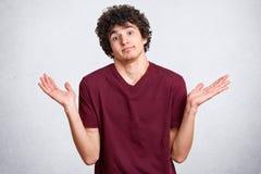 Svart haired karismatisk angen?m ung man med det lilla sk?gget och att rycka p? axlarna h?nder med desperation som ser direkt p?  fotografering för bildbyråer