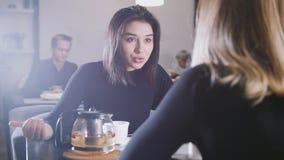 Svart haired ung kvinna med svart hår som dricker kaffe och talar med flickvännen i kafét Arkivfoto