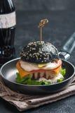 Svart hamburgare med den grillade fega lilla pastejen Royaltyfria Bilder