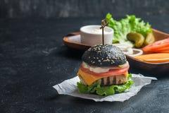 Svart hamburgare med den grillade fega lilla pastejen Arkivfoto