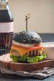 Svart hamburgare med den grillade fega lilla pastejen Arkivfoton