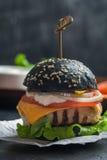 Svart hamburgare med den grillade fega lilla pastejen Royaltyfri Bild