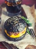 Svart hamburgare med drinken Arkivbilder