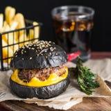 Svart hamburgare med nötkött och ost Fotografering för Bildbyråer
