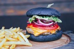 Svart hamburgare med pommes frites och sås på ett träbräde arkivfoton