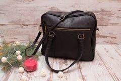 Svart handväska på en träbakgrund, granfilial, girland och stearinljus Royaltyfri Fotografi