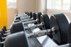 Svart hanteluppsättning på kuggeslut upp i begrepp för utrustning för utbildning för vikt för sportkonditionmitt arkivfoto