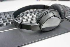 Svart headphone på tangentbordet Royaltyfri Fotografi