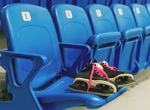 Svart hockey åker skridskor med knackar kängsnören på stolen på den tomma stadion Rader har en beräkning royaltyfri fotografi