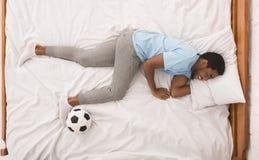 Svart idrottsman med bollen som sover på säng royaltyfri fotografi