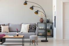 Svart industriell lampa bredvid den gråa soffan med mönstrade kuddar, kaffetabellen och puffen i monochromatic vardagsrum royaltyfri bild