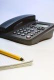 Svart IP-telefon, anteckningsbok och penna Arkivfoto