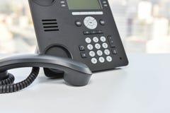 Svart IP-telefon på den vita tabellen Royaltyfria Bilder