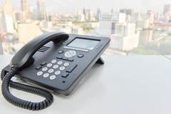 Svart IP-telefon på den vita tabellen Arkivfoto