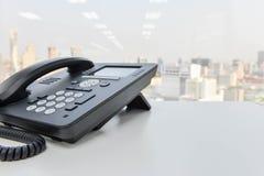 Svart IP-telefon på den vita tabellen Arkivfoton