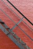 Svart järntrappuppgång mot en vägg för röd tegelsten arkivbild