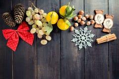 Svart julbakgrund med tomt kopieringsutrymme Druvor, tangerin och muttrar royaltyfria bilder