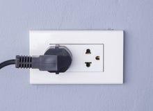 Svart kabel pluggade in ett vitt elektriskt uttag som monterades på grå färger w Arkivbild