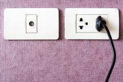 svart kabel pluggade in ett vitt elektriskt uttag som monterades på rosa färger w Arkivbilder