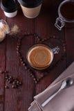 Svart kaffe bland hjärta formade kaffebönor Fotografering för Bildbyråer