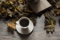 Svart kaffe en bok och höstsidorna, höstbakgrund royaltyfria foton