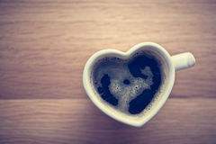 Svart kaffe, espresso i hjärta formade koppen Förälskelse valentin dag, tappning Royaltyfri Foto