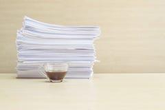 Svart kaffe för Closeup i genomskinlig kopp kaffe och hög av arbetspapper i arbetsbegrepp på det suddiga den texturerade träskriv Fotografering för Bildbyråer