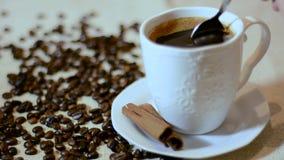 Svart kaffe för skedblandning i den vit koppen och kanel på tefatet och grillade kaffebönor arkivfilmer