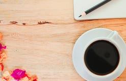 Svart kaffe i den vita exponeringsglas och blyertspennan på boken på trätabellbakgrund Arkivfoto