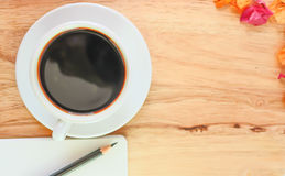 Svart kaffe i den vita exponeringsglas och blyertspennan på boken på trätabellbakgrund Royaltyfri Foto