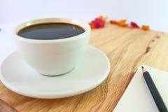 Svart kaffe i den vita exponeringsglas och blyertspennan på boken på trätabellbakgrund Royaltyfri Fotografi