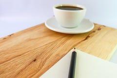 Svart kaffe i den vita exponeringsglas och blyertspennan på boken på trätabellbakgrund Arkivbilder