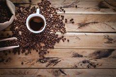 Svart kaffe i den vita koppen, med kaffebönor på träbakgrund, bästa sikt, kopieringsutrymme royaltyfri bild
